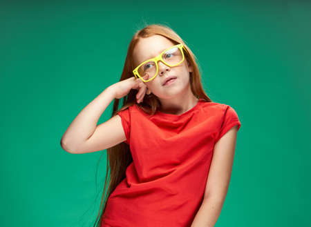 cute red-haired girl gesturing with her hands childhood green background school Foto de archivo