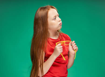 girl with red hair holding yellow glasses in her hands green background studio red t-shirt