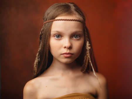 The girl on a red background with an ornament on the head of a feather aborigines savage Foto de archivo