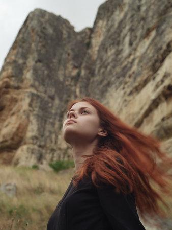 Side view portrait of woman in black dress on nature in mountains Foto de archivo