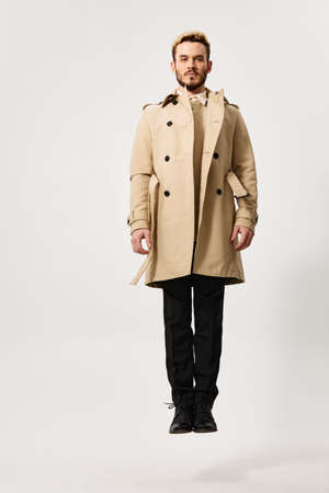 a guy in a coat trousers flew up on a light background