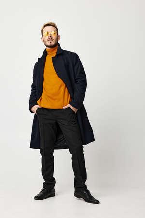 confident man in coat orange sweater pants shoes model glasses