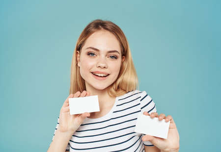 Woman with business cards of different sizes on a blue background and a striped T-shirt