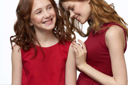 Cheerful mom and daughter in red dresses socializing light background