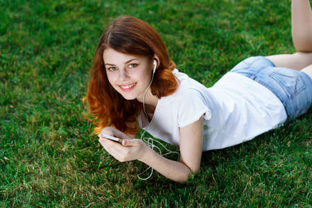woman lies on the lawn with a phone in her hands relaxing in the park