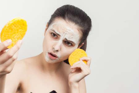 cheerful brunette with shoulders face mask sponges in hands skin care Foto de archivo