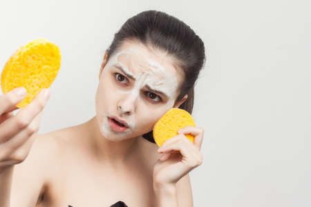 cheerful brunette with shoulders face mask sponges in hands skin care Stock Photo