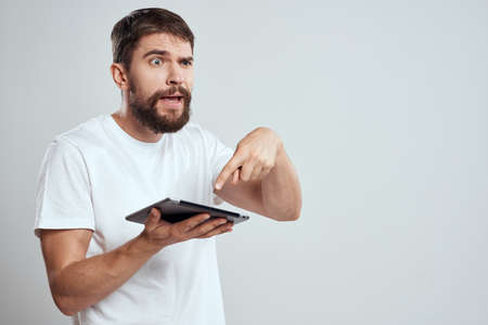 A bearded man in a white t-shirt a tablet in the hands of a professional manager communication technology
