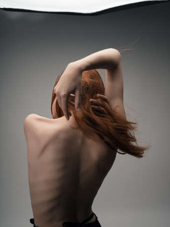 Nude red-haired woman touching herself with hands cropped back view