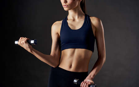 woman with muscles doing sports dumbbells in her hands and slim figure