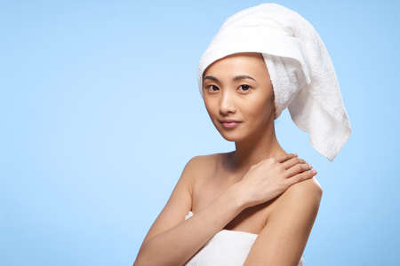 woman asian appearance towel on head clean skin spa treatments blue background