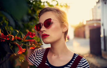 beautiful woman in glasses near red flowers on the street and red sundress striped t-shirt Foto de archivo