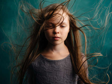 Pretty little girl with disheveled hair on a turquoise background