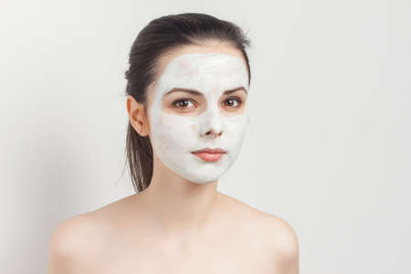 pretty brunette with cream face mask shoulders smile cropped view