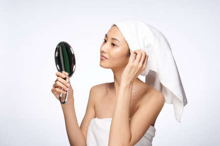 pretty woman with a towel on her head looking in the mirror skin care health hygiene