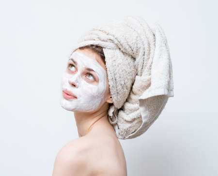 happy woman with towel on head shoulders moisturizer on face mask