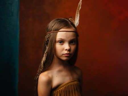 The girl on a red background with an ornament on the head of a feather Standard-Bild