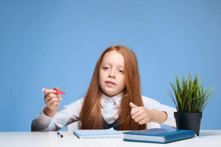 red-haired girl sitting at study table education lifestyle learning Imagens