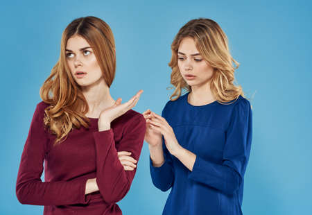two girlfriends in dress conflict emotions blue background studio