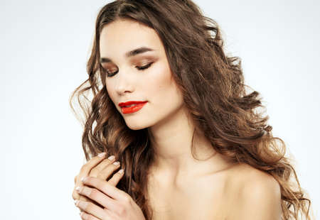 Woman with closed eyes evening makeup eye shadow on eyelids with brunette curly hair