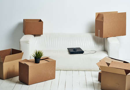 Boxes with things white sofa unpacking office moving Standard-Bild