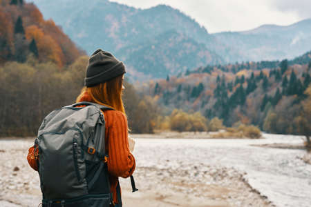 woman with a backpack near the river on nature in the mountains