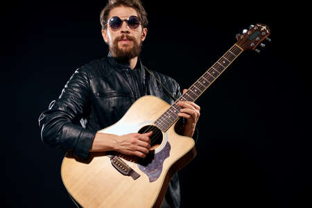man with a guitar in his hands black leather jacket sunglasses music emotions black background Imagens