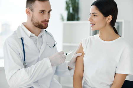male doctor with syringe in hand and female patient injection vaccine infection