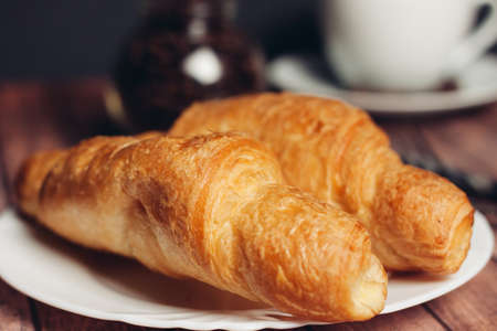 fresh croissants on a saucer table setting breakfast cup with drinks