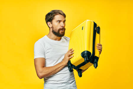 bearded man in white t-shirt yellow suitcase passenger isolated background
