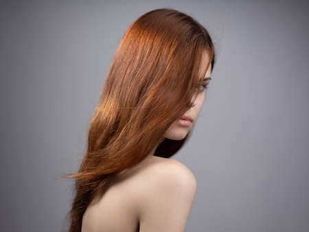fashionable woman with red hair shoulders side view Stockfoto