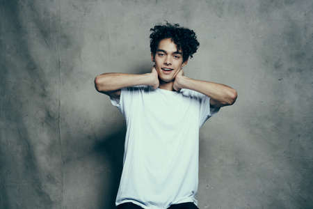 Cheerful guy with curly hair gestures with his hands near his face on a gray fabric background in a white t-shirt Standard-Bild