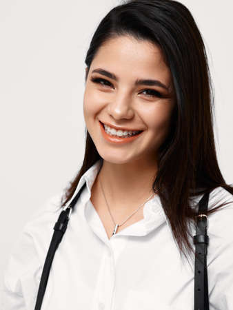 happy woman in white shirt with suspenders laughs and makeup on face
