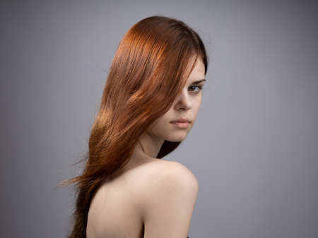 Beautiful woman with loose red hair on a gray background bared shoulders portrait