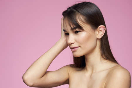 beautiful brunette shoulders clear skin pink background cropped view