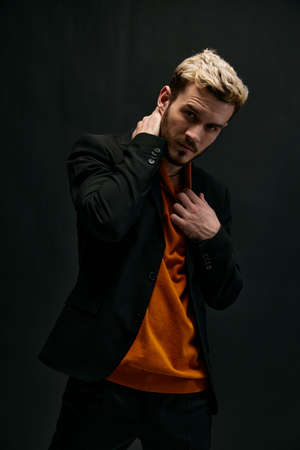 blond guy in an orange sweater and jacket on a dark background holds his hand behind his head Imagens