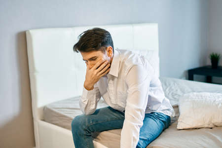 upset man indoors on the bed touching his face with his hand loneliness sadness