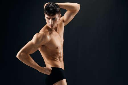 man with a pumped-up torso athlete dark background studio
