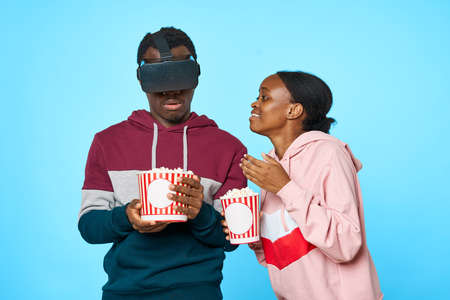 man and woman african appearance virtual reality glasses popcorn entertainment