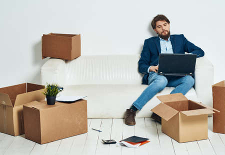 Man sitting on sofa with laptop office boxes with things work