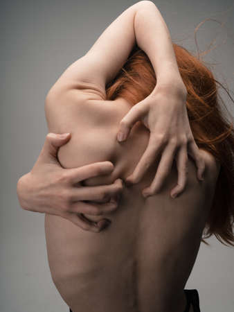 A thin woman touches herself behind her back with her hands with emotion model Foto de archivo