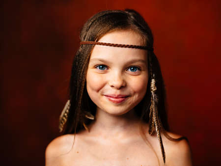 wild girl with feather in her hair smile loose hair indian culture Standard-Bild