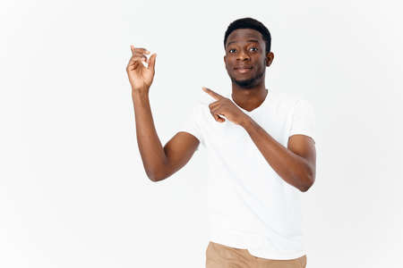 handsome guy of African appearance shows a finger to the side on a light background and beige trousers