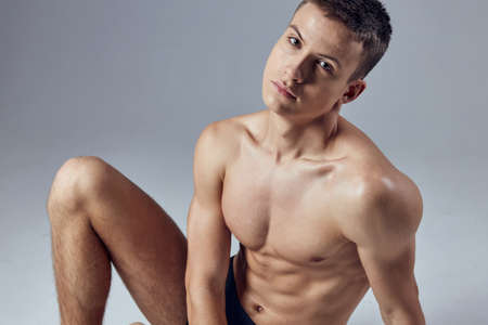 handsome male athlete with a pumped-up body sitting on the floor