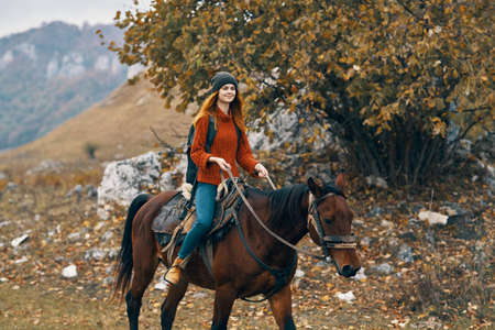woman hiker riding horse mountains landscape travel adventure