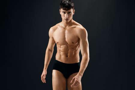a man in dark shorts with a muscular body on a dark background bodybuilder. High quality photo