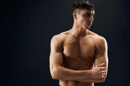 sporty man pumped up body workout bodybuilder dark background