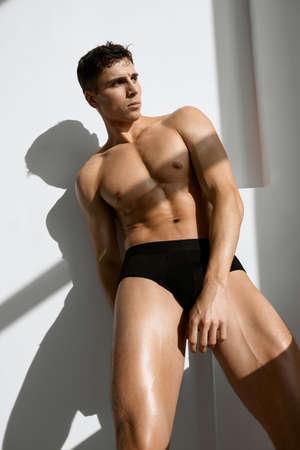 a man in dark shorts with a pumped-up body macho bodybuilder Foto de archivo