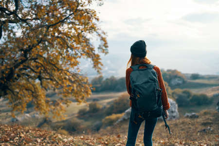 woman hiker with backpack admires nature mountains landscape Foto de archivo