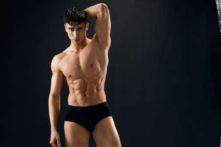 sporty man in dark shorts phasing Studio dark background. High quality photo Stock Photo